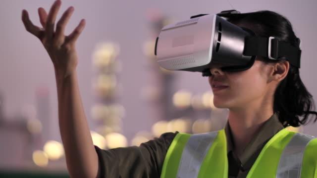 夜間に石油産業プラントでバーチャルリアリティヘッドセットを着用した女性エンジニア - コントロール点の映像素材/bロール
