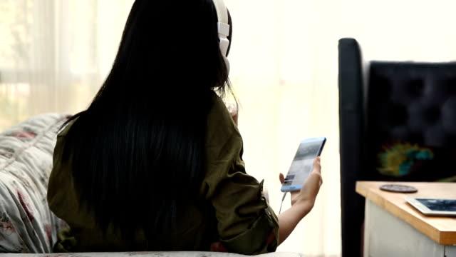 女性は、音楽を聴いて楽しむ - アイスティー点の映像素材/bロール