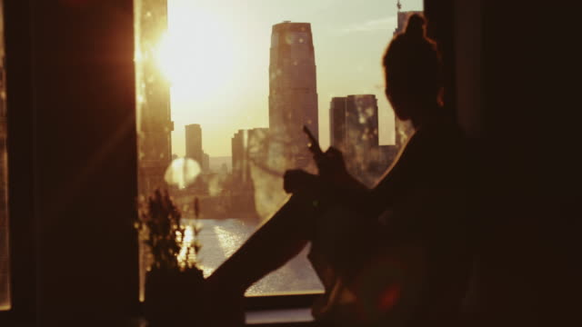 vídeos de stock e filmes b-roll de woman enjoy sunset in new york from home - janela