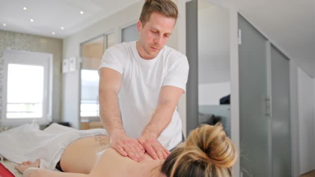 woman enjoying a back massage - viziarsi video stock e b–roll