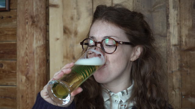 vídeos de stock e filmes b-roll de woman enjoying a beer in cosy mountain hut - beer alcohol