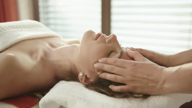 woman enjoying a head massage at a spa - head massage stock videos and b-roll footage