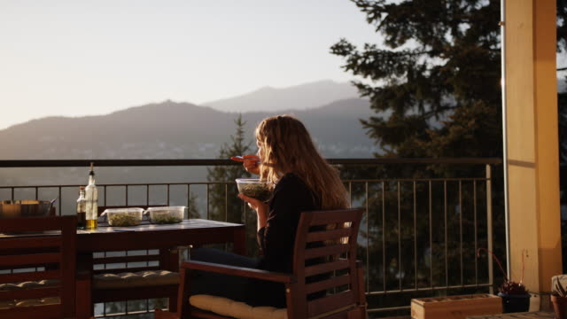 vídeos de stock, filmes e b-roll de mulher desfrutando de uma salada de microverdes ao pôr do sol por trás - cabelo louro