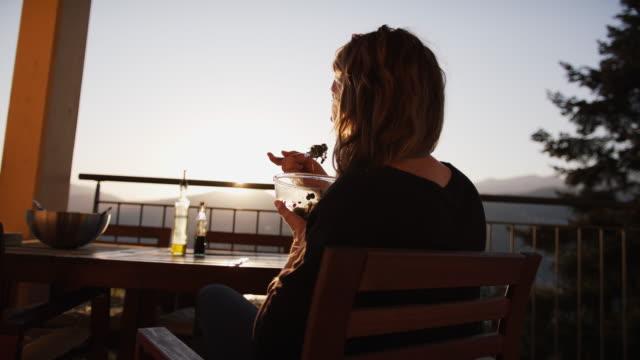 stockvideo's en b-roll-footage met vrouw die van een salade van microgreens bij zonsondergang van achter geniet - balkon