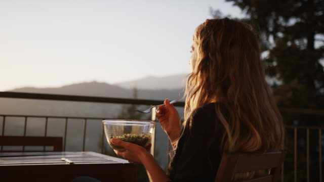woman enjoying a salad of microgreens at sunset on balcony - salad bowl stock videos & royalty-free footage
