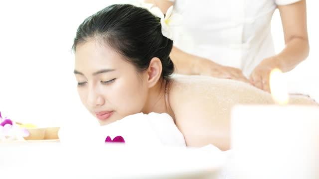 塩を楽しんでいる女性は、リラックスのためのマッサージをスクラブします。 - マッサージ台点の映像素材/bロール