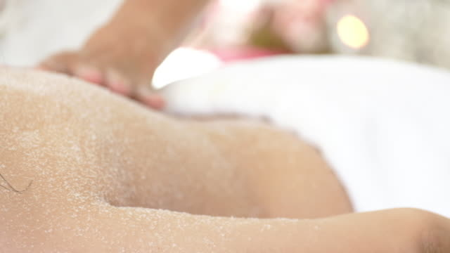 vídeos de stock e filmes b-roll de woman enjoying a salt scrub massage for relax. - spa treatment