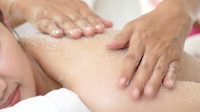 woman enjoying a salt scrub massage for relax. - scrubs stock videos & royalty-free footage
