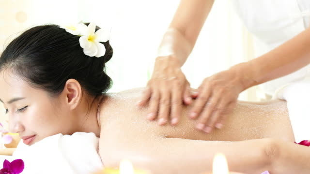 woman enjoying a salt scrub massage for relax. - massage table stock videos and b-roll footage