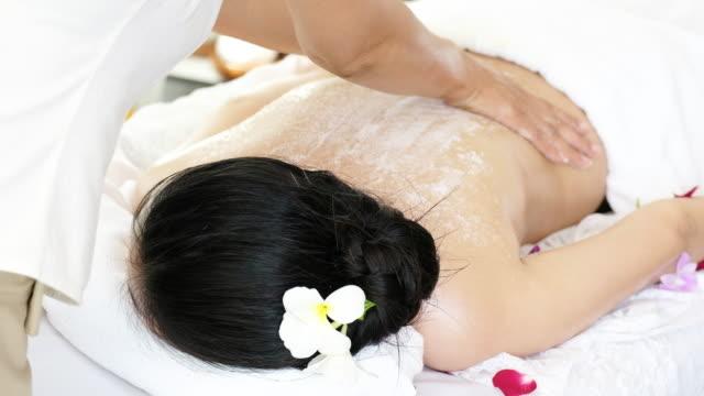 woman enjoying a salt scrub massage for relax.apply salt on the back - exfoliation stock videos & royalty-free footage