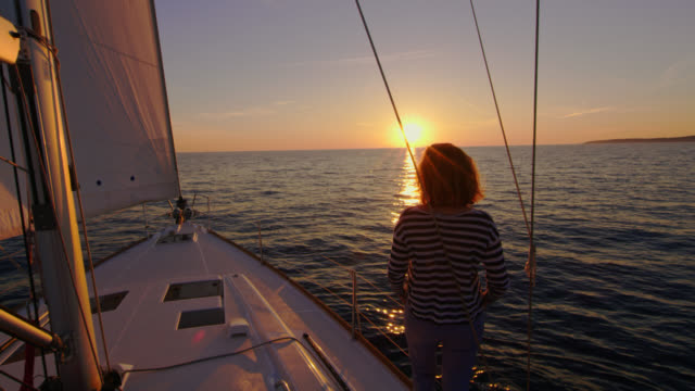 slo mo woman enjoying a view of a beautiful sunset on a sailboat - ship's bow stock videos and b-roll footage