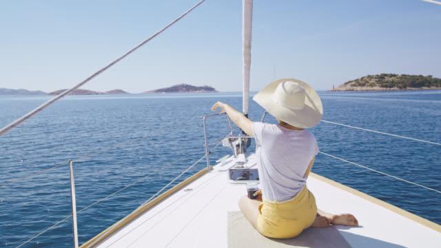 Mujer DS disfruta de una vista en la cubierta de un velero