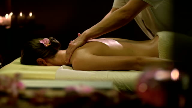 woman enjoying an oil back massage - massage table stock videos & royalty-free footage