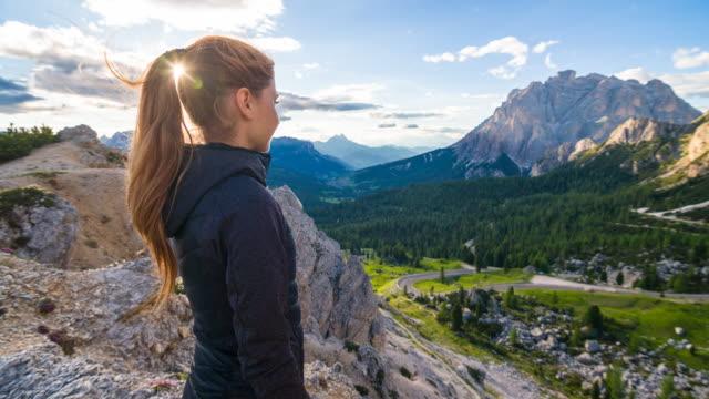 frau genießen atemberaubende aussicht vom gipfel eines berges mit blick auf ein tal - jacke stock-videos und b-roll-filmmaterial