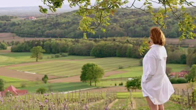 SLO MO femme appréciant l'air frais au sommet d'une colline