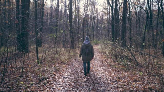 晴れた秋の日に森に散歩しながら新鮮な空気を楽しむ女性