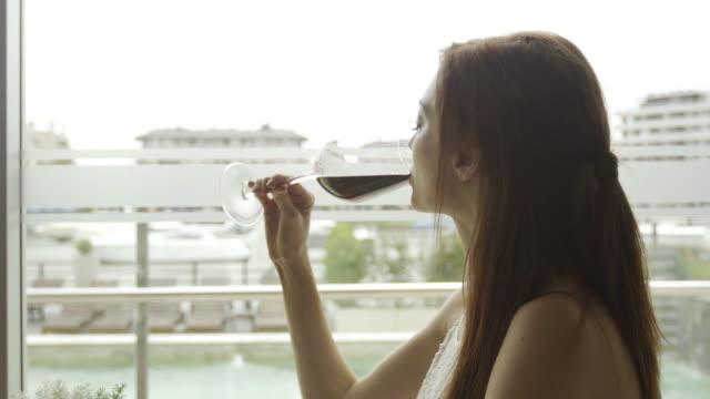 woman enjoying glass of red wine slow motion - ワインバー点の映像素材/bロール