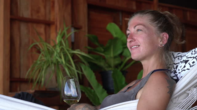 woman enjoying glass of white wine relaxing in hammock - refreshment stock videos & royalty-free footage