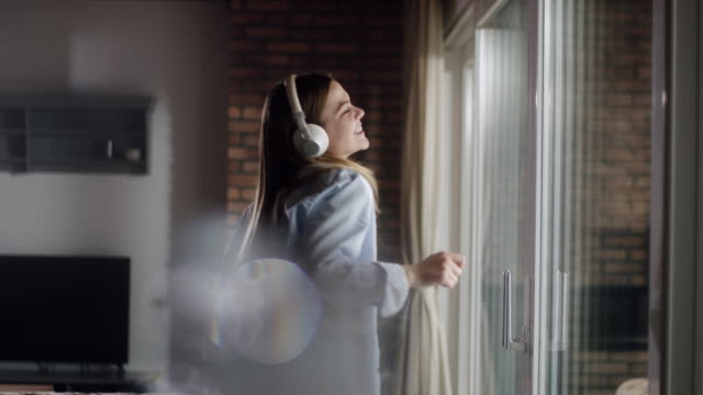 woman enjoying her favorite music - cuffia attrezzatura per l'informazione video stock e b–roll