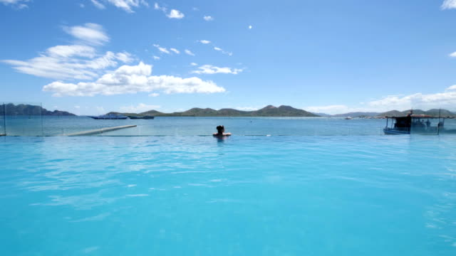 woman enjoying her summer holidays at an infinity pool - infinity pool stock videos & royalty-free footage