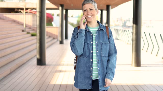 woman enjoying her walk by the river and telephoning - short hair stock videos & royalty-free footage