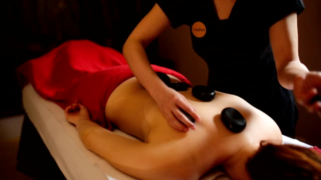 vídeos de stock, filmes e b-roll de mulher desfrutando de terapia de massagem com pedras quentes - lastone therapy