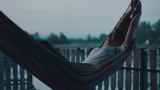 woman enjoying in hammock at lake house - hammock stock videos & royalty-free footage