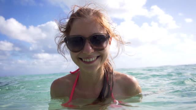 woman enjoying in the sea kisses the camera - bikini stock videos & royalty-free footage