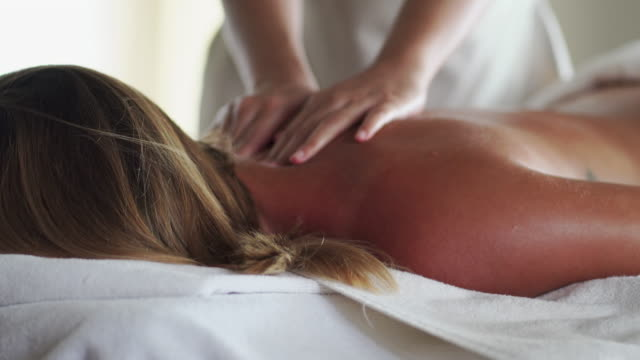 woman enjoying massage on her back and shoulder in spa - massage table stock videos & royalty-free footage