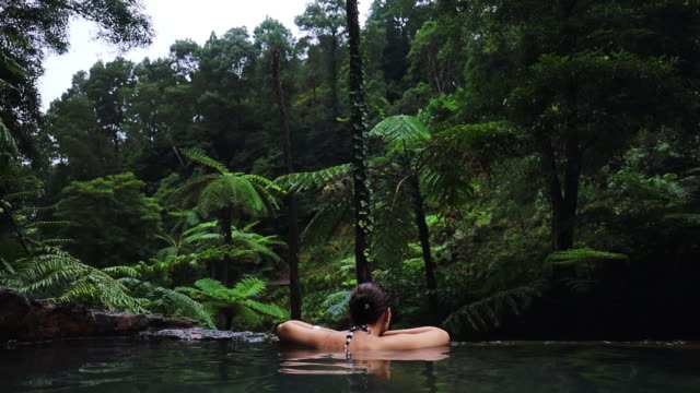 woman enjoying natural hot spring in the middle of rainforest in the azores islands. - atlantikinseln stock-videos und b-roll-filmmaterial