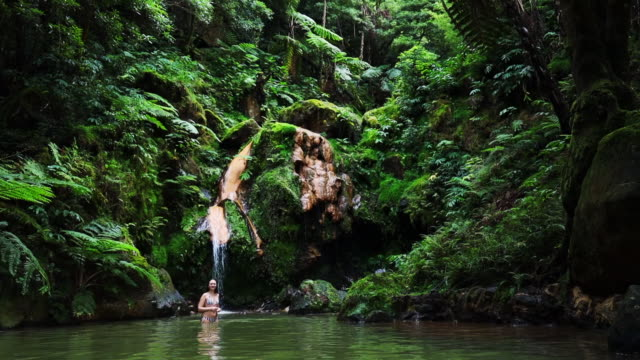 vidéos et rushes de woman enjoying natural hot spring with waterfall in the azores islands. - îles de l'atlantique