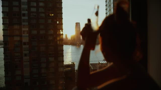 woman enjoying new york at the window - twilight stock videos & royalty-free footage