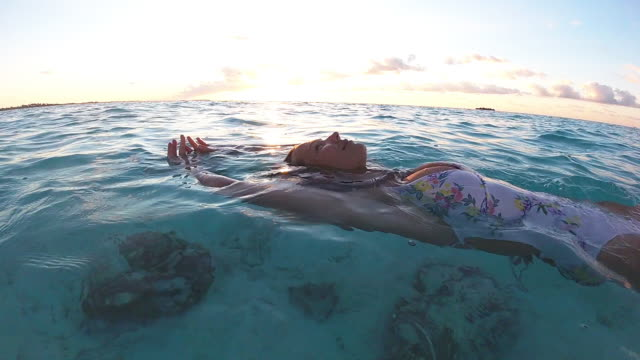 vidéos et rushes de femme appréciant l'océan au coucher du soleil - tête composition