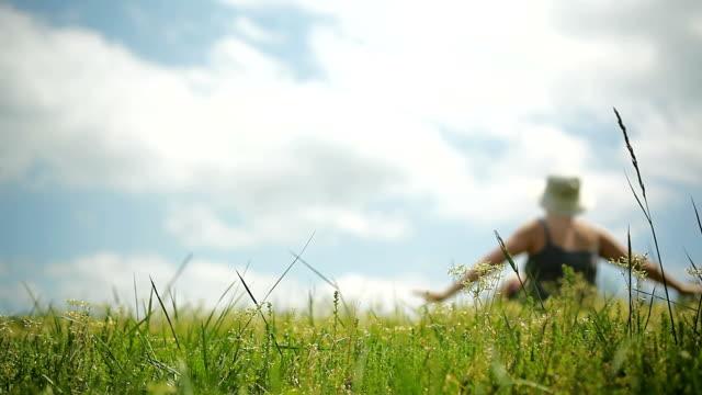 vídeos de stock e filmes b-roll de woman enjoying outdoor life sitting on grass - só uma mulher madura