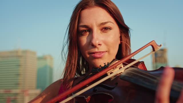vídeos de stock, filmes e b-roll de mulher curtindo sessão de violino no telhado, sorrindo para uma câmera. diversão de verão - violino