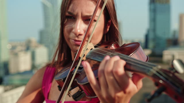 woman enjoying rooftop violin session. summer fun - roof stock videos & royalty-free footage