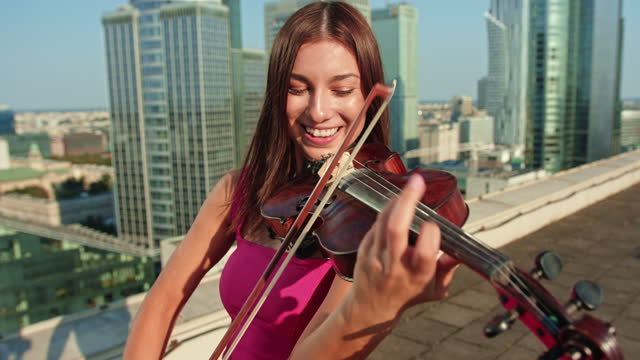 woman enjoying rooftop violin session. summer fun - musician stock videos & royalty-free footage