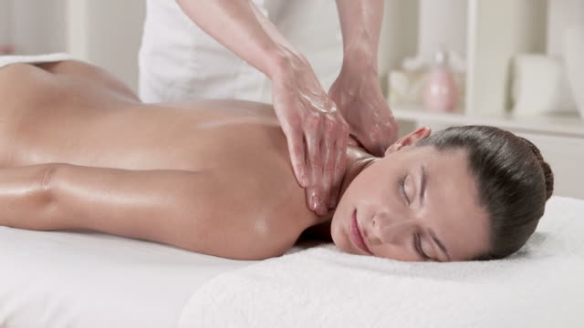 hd dolly: woman enjoying shoulder and neck massage - massage table stock videos & royalty-free footage