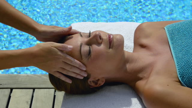 woman enjoying spa treatment-head massage. - massaging stock videos & royalty-free footage