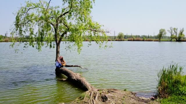 woman enjoying summer day sitting on willow in lake - appoggiarsi video stock e b–roll
