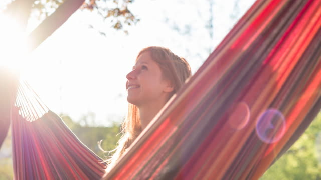 Woman enjoying summer in nature, sitting in a hammock