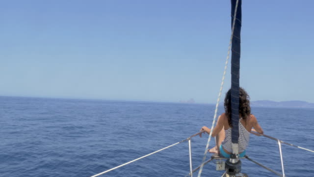 woman enjoying summer on a sailboat - 小型船舶点の映像素材/bロール