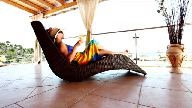 stockvideo's en b-roll-footage met hd crane: woman enjoying summer vacations by the swimming pool - tropische drankjes