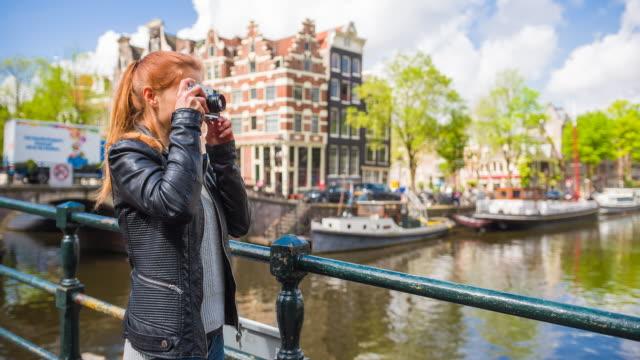 vidéos et rushes de femme appréciant la journée ensoleillée, admirant des canaux d'amsterdam, prenant des photos avec l'appareil-photo analogique rétro de vieille école - photographe