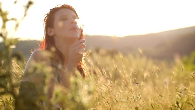 vídeos de stock, filmes e b-roll de mulher, aproveitando o dia ensolarado de verão no campo - soprando