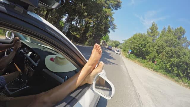 vídeos de stock, filmes e b-roll de ms woman aproveitando a viagem de verão ensolarado com pés para fora da janela do carro - de pé para cima