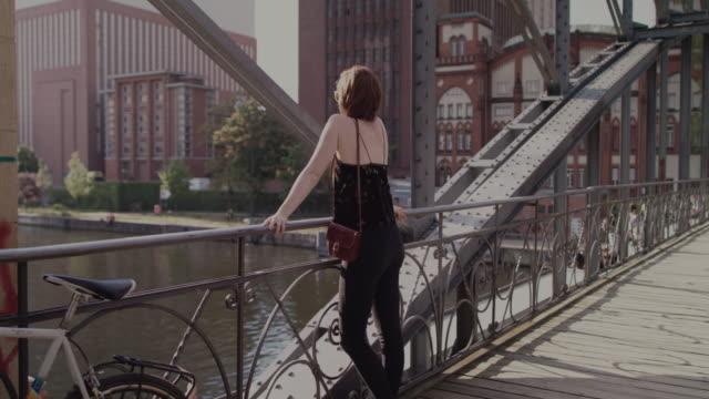 Woman enjoying sunshine on bridge