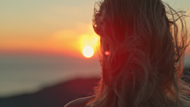 time warp woman enjoying the amazing seaview at sunset - blonde hair stock videos & royalty-free footage