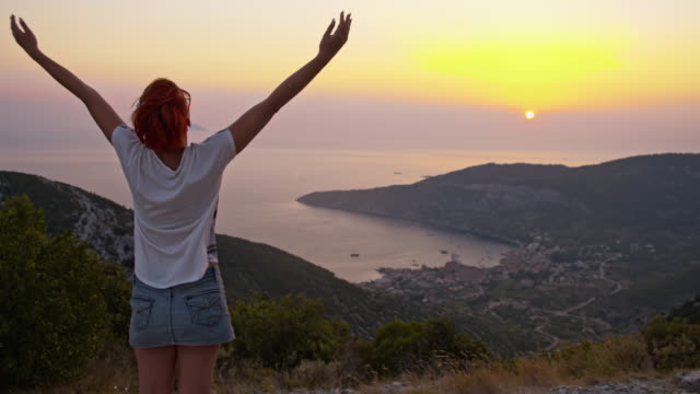 slo mo woman enjoying the freedom at sunset - arms raised stock videos & royalty-free footage