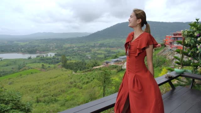 vídeos de stock, filmes e b-roll de mulher que aprecia a opinião da infinidade em um vestido ventoso do dia no vento - modelo profissional